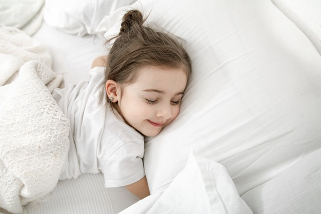 cute-little-girl-is-sleeping-white-bed_169016-6449