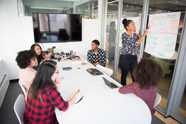 Ľudia sediaci v kancelárii s posuvnými dverami za stolom