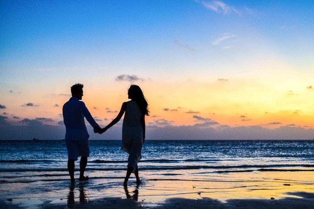 Muž a žena držiaci sa za ruky sa prechádzajú po pláži.jpg