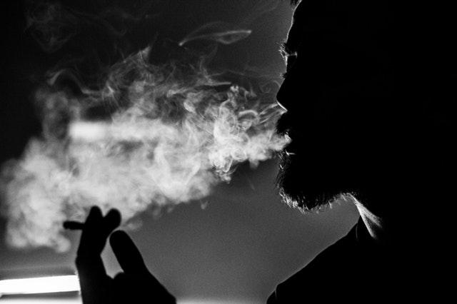 Muž s cigaretou v ruke vyfukuje dym z úst.jpg
