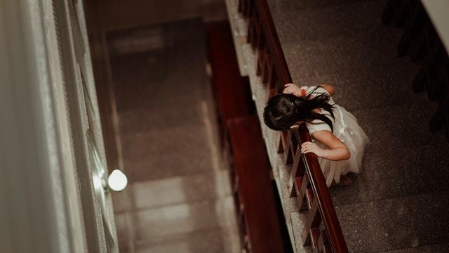 Dievčatko v bielych šatách stojí na chodoch a pozerá dole cez zábradlie.jpg