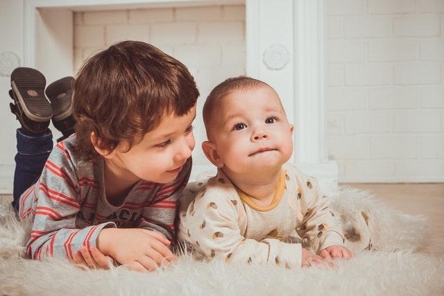 Malé bábätko v bielych dupačkách leží vedľa staršieho chlapčeka.jpg