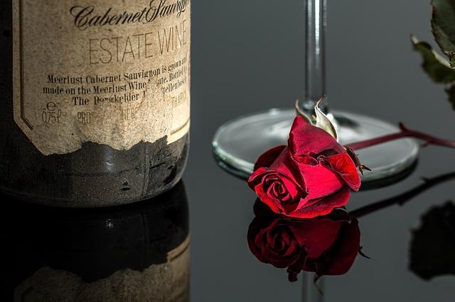 fľaša vína pri ruži
