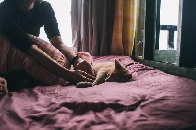 Žena sedí v posteli a hrá sa s mačkou