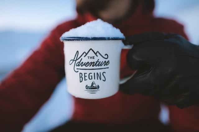 Muž v bunde drží hrnček so snehom a nápisom the adventure begins.jpg