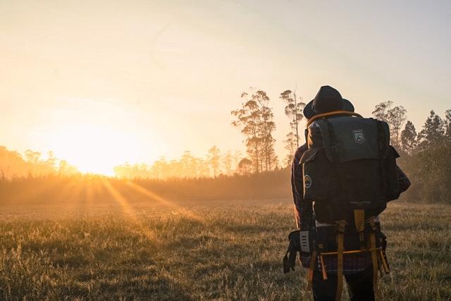 Muž s klobúkom, veľkým batohom stojí na lúke počas východu slnka.jpg