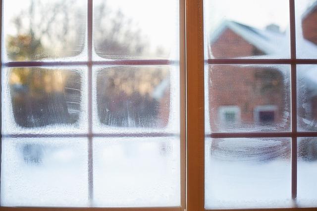 Zamrznuté okná, za ktorými je zasnežená krajina.jpg