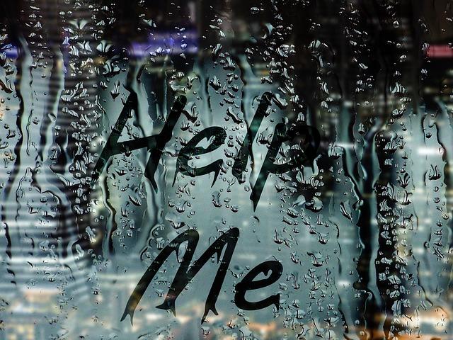 Okno pokryté kvapkami vody s nápisom help me.jpg